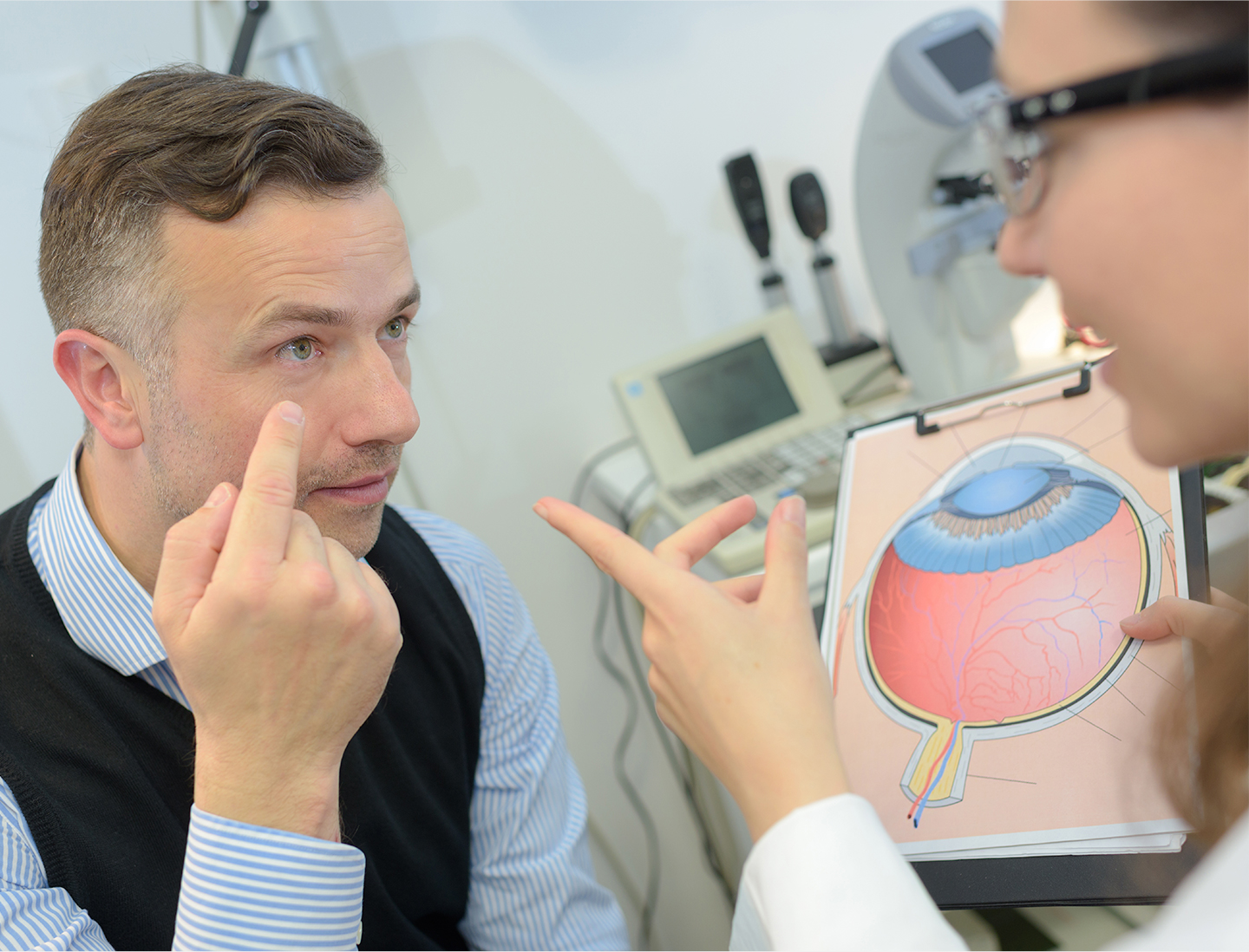 Image of male patient discussing eyes with female doctor.