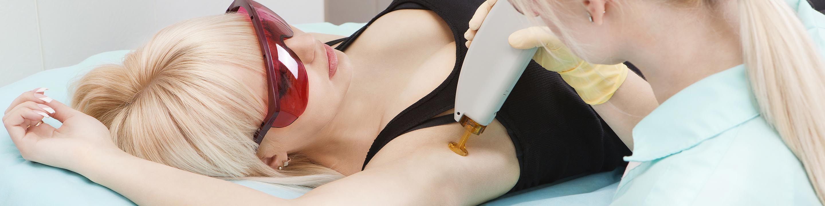 Woman having laser skin treatment on her arm.
