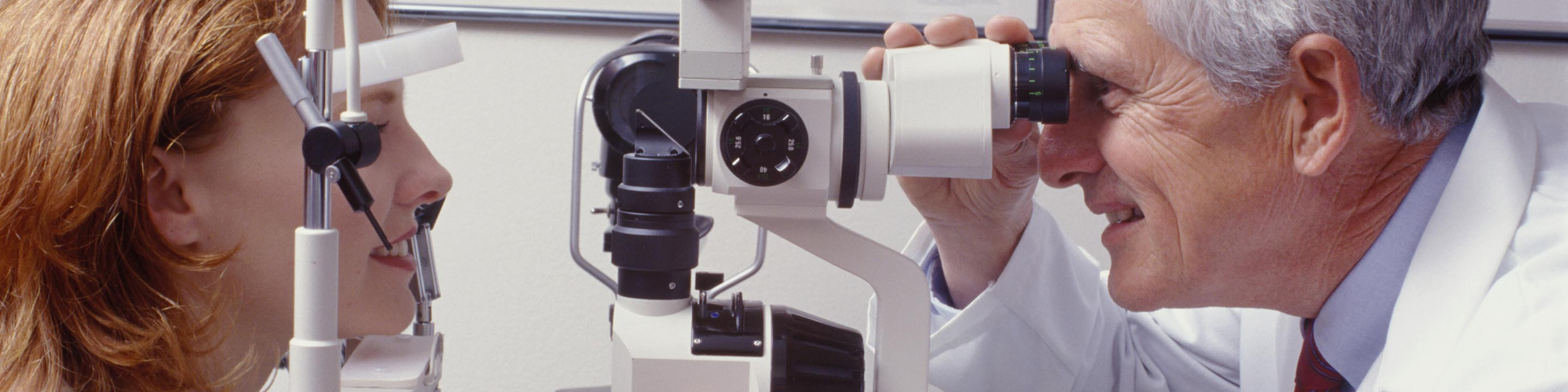 Image of doctor performing eye exam on female patient.