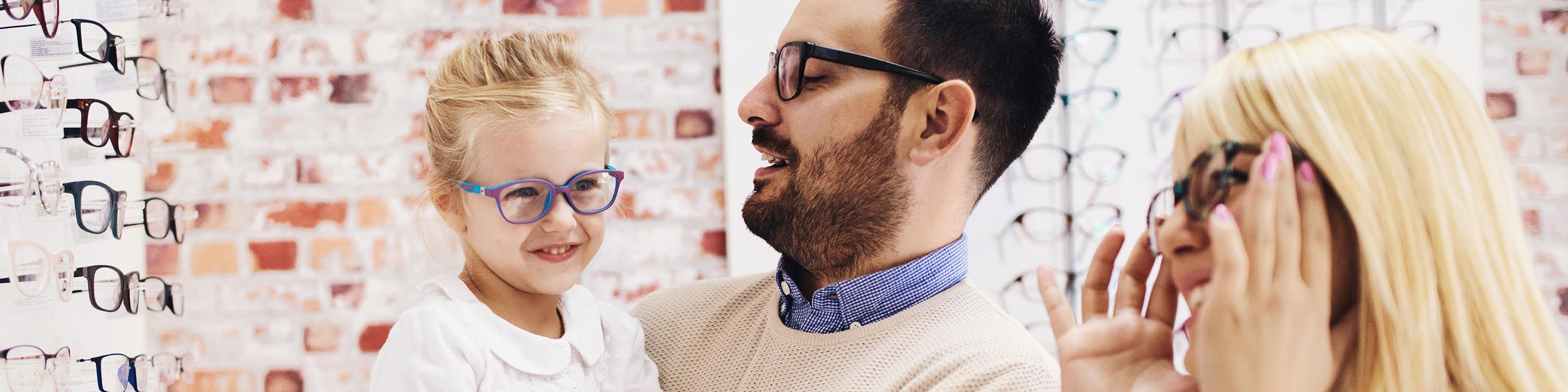 Image of daughter with father and mother trying on eye glasses.
