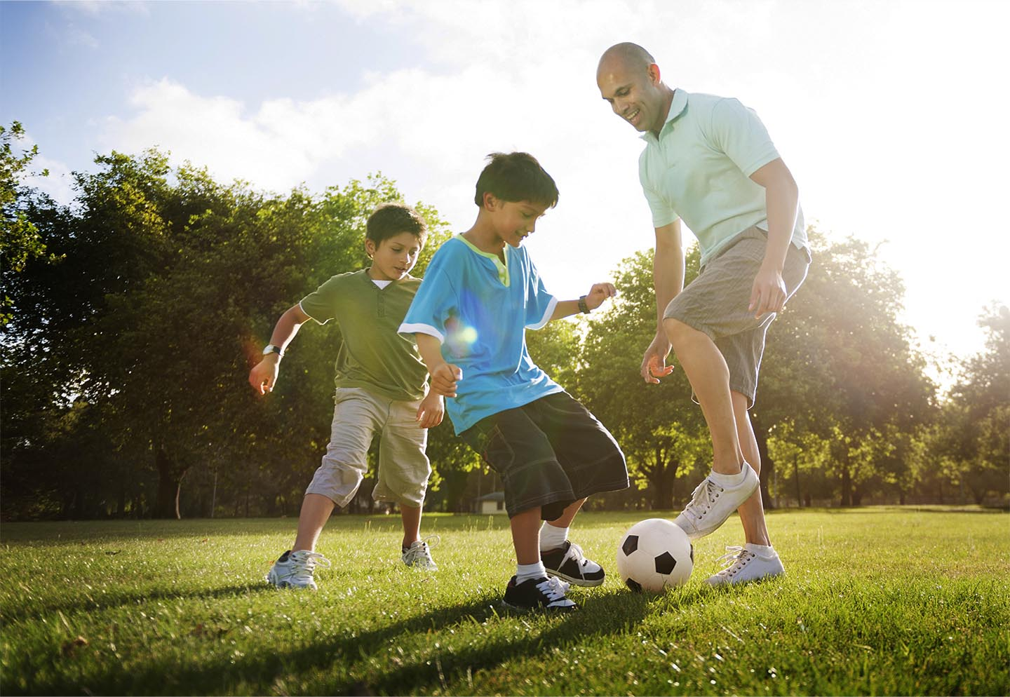 Image of father and sons playing soccer.
