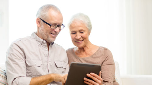 Elderly man and woman looking at a tablet.